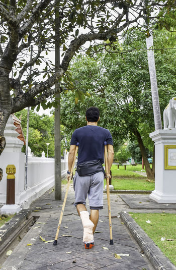 Rear view full length of man walking with crutches on footpath at park