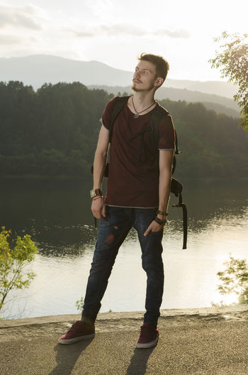 Young man on a lake shore with rucksack during the sunset Activity Adventure Backlight Backpack Casual Clothing Caucasian Ethnicity Handsome Jeans Kayak Lake Leisure Activity Nature One Person Outdoor Recreation  Reflections Rucksack Shore Sneakers Summertime Sundown Tranquil Scene Watch Water Young Men