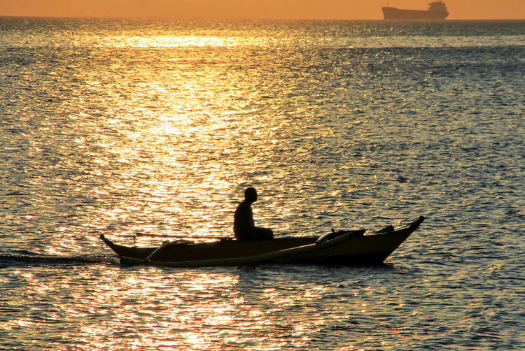 Sunset Water Sea Silhouette Nautical Vessel Nature Beauty In Nature Mode Of Transport Sunlight Transportation Outdoors One Person Wave Real People One Man Only People Adults Only Adult Day
