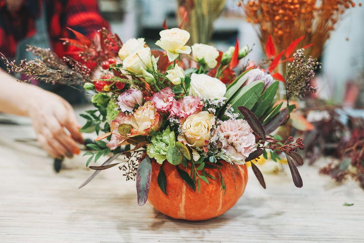 Diy autumn flower arrangement bouquet in pumpkin, florist at work, floristry studio