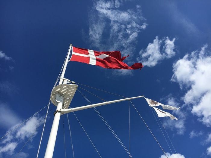 Low angle view of danish flag waving on sailboat against sea