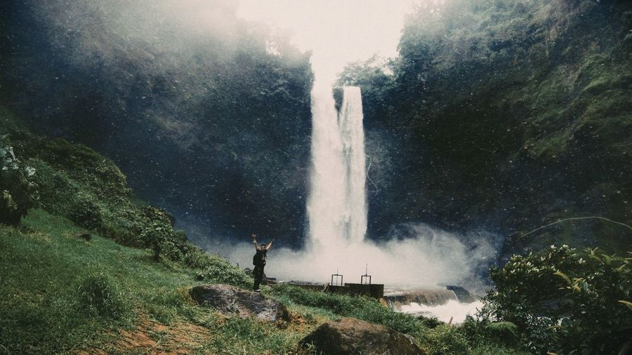 Full length of man standing by waterfall against trees