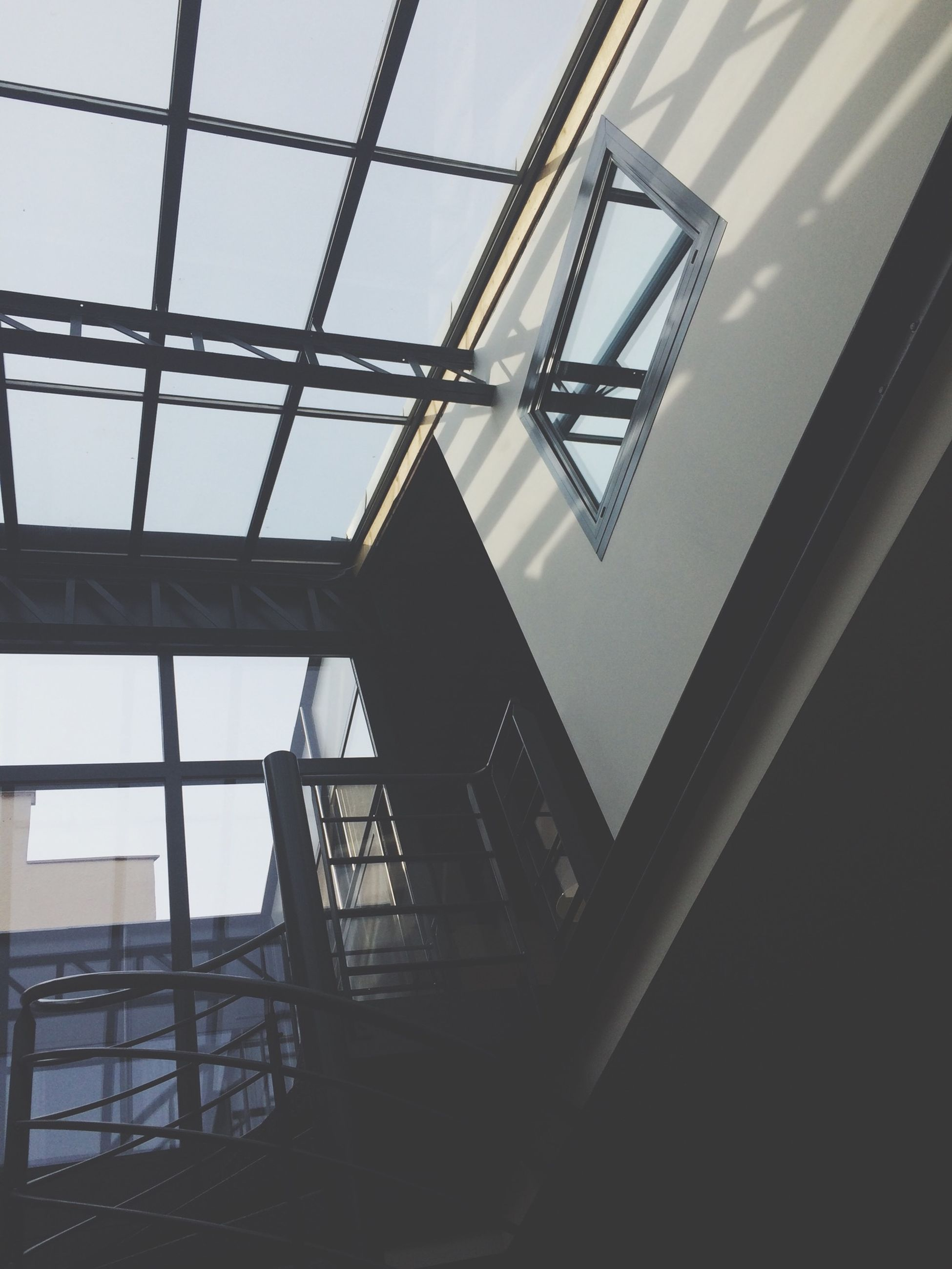 architecture, built structure, low angle view, building exterior, indoors, window, building, metal, glass - material, sky, railing, directly below, pattern, day, architectural feature, no people, modern, geometric shape, clear sky, ceiling