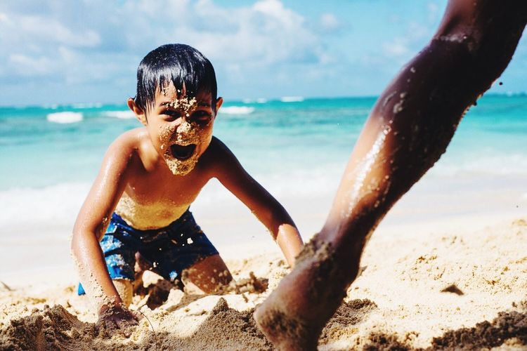 Boy With Sand On Face Screaming While Kneeling At Beach