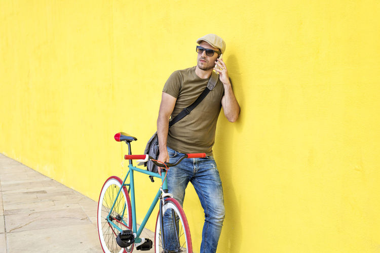 Side view of a young adult man with a vintage bike and wearing casual clothes and sunglasses standing against a yellow wall while using a mobile phone in a sunny day Bicycle One Person Casual Clothing Young Adult Transportation Yellow Holding Sport Young Men Standing Men Front View Copy Space Architecture Activity Adult Wall - Building Feature Technology Jeans Outdoors Young Man Hipster Trendy Fashionable Hat T-shirt Shoulder Bag Sunglasses Mobile Phone Smartphone Using Phone Standing Retro Fixie Vintage Looking Away Jeans