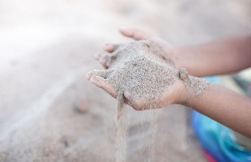 Sand puffs through the fingers of a girl's hand.