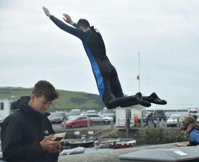 Real People Communication Wireless Technology Leisure Activity Day Sky Holding Men Technology Outdoors Lifestyles Mobile Phone Portable Information Device Young Men Togetherness Harbour Wall Harbour Wall Jumping Young Adult Architecture People Sea Childhood Cornwall Uk Sea Swimming St Mawes Harbour