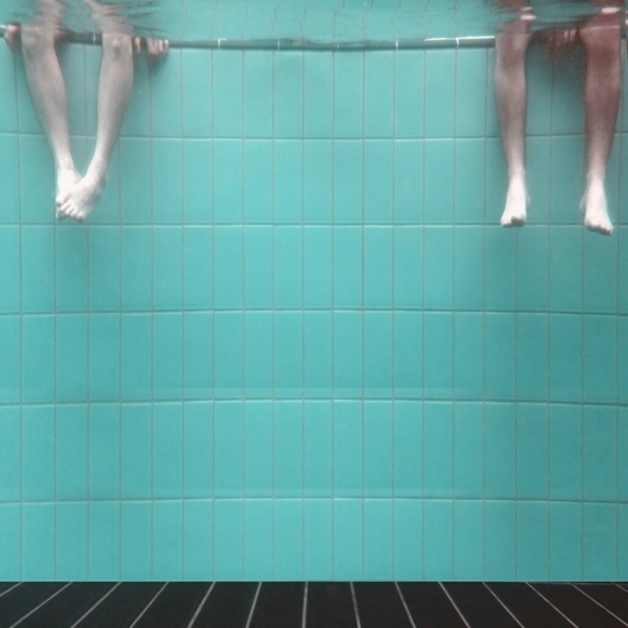 Underwater view of legs dangling in swimming pool