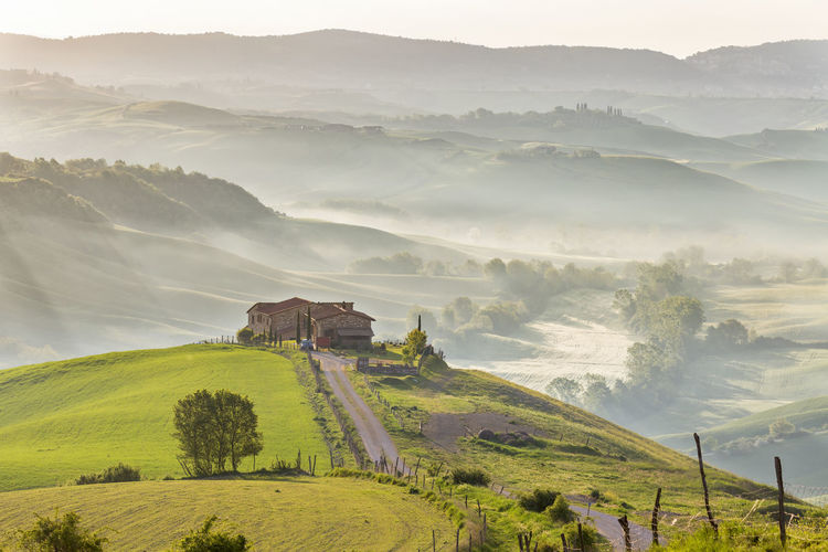 Tuscan farm landscape with morning fog in the rolling landscape
