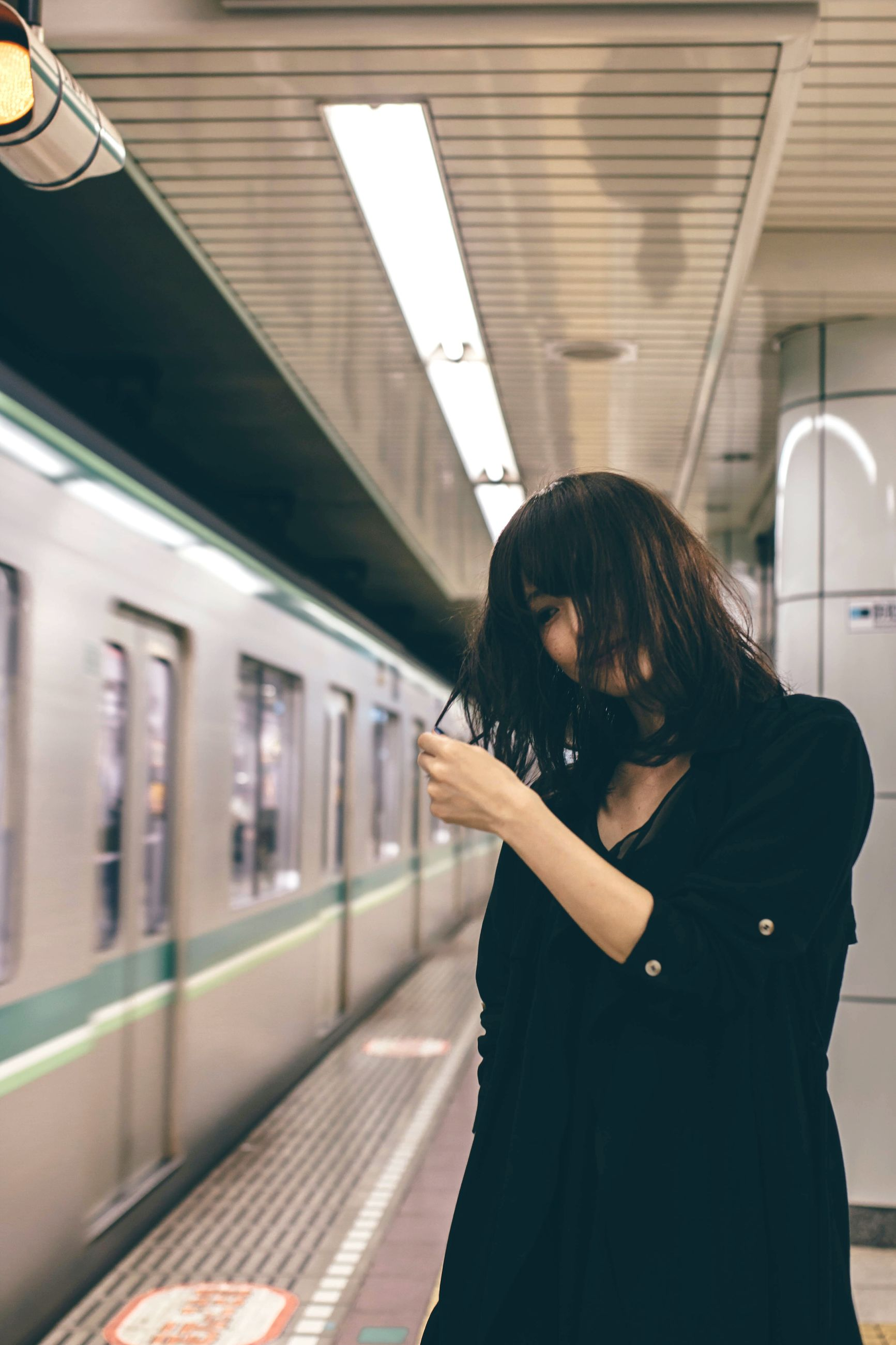 one person, young adult, holding, indoors, adults only, only women, one woman only, transportation, standing, adult, one young woman only, subway train, people, real people, women, young women, human hand, public transportation, day