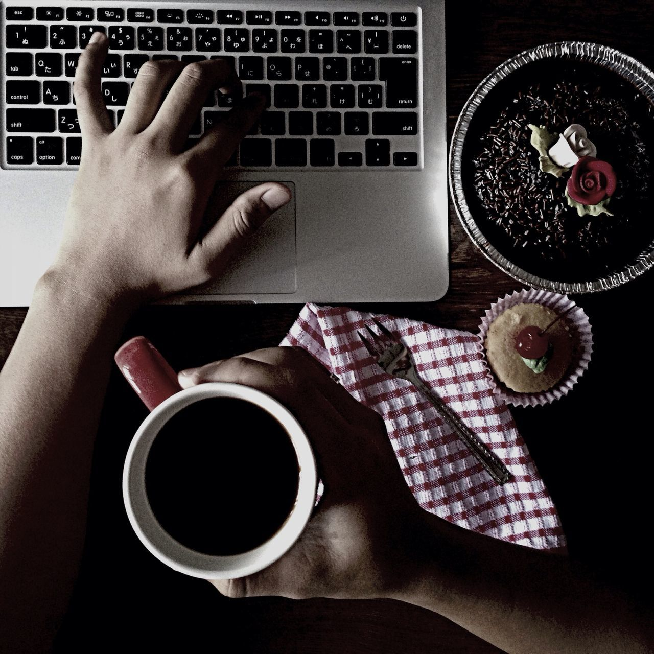 High angle view of man using laptop while holding coffee