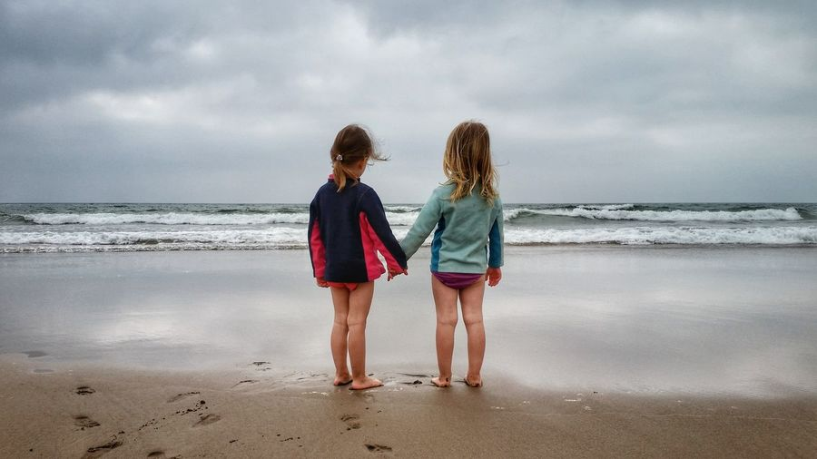Rear view of girls on beach against sky