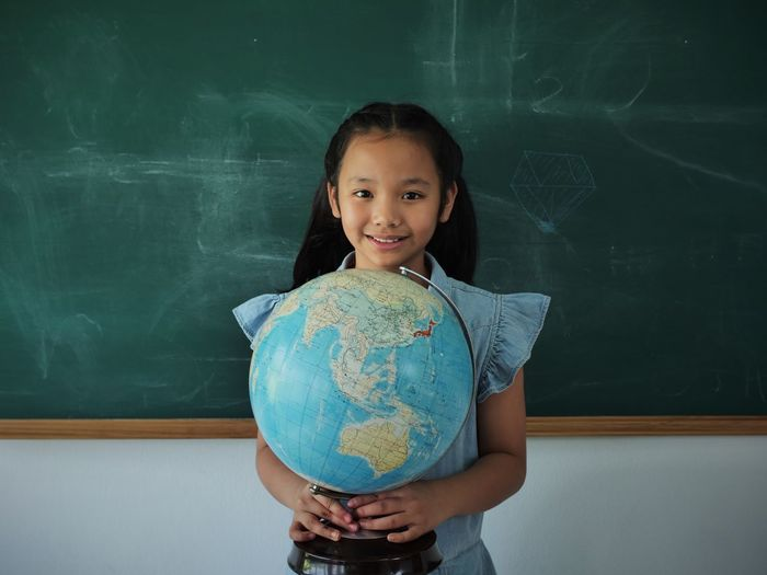 Portrait of smiling girl holding globe while standing in classroom