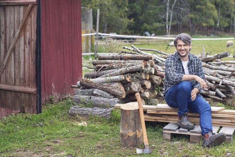 Portrait of smiling man sitting on log
