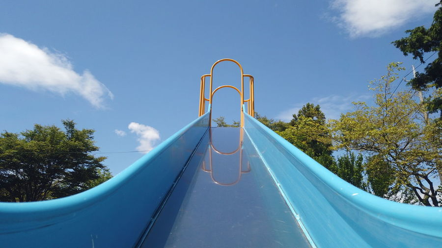 Low angle view of playground against blue sky