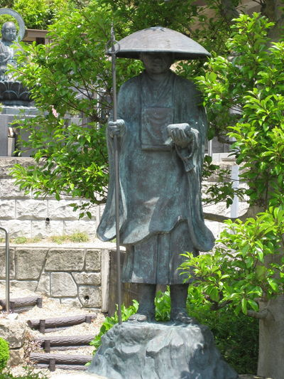 Statue of a buddhist monk in traditional garb consisting of robe, staff, straw hat and prayer beads in Tsuruga, Japan. ALMS Japan Spirituality Staff Alms Giving Bronze Statue Buddhism Human Representation Monk  No People Outdoors Praying Beads Religion Religion And Beliefs Robe Statue Straw Hat Zori