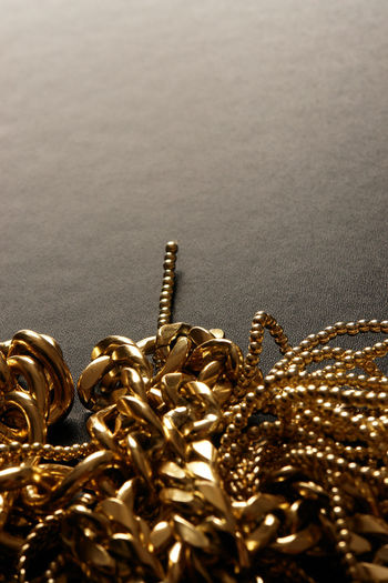 Close-Up Of Tangled Gold Chains On Table