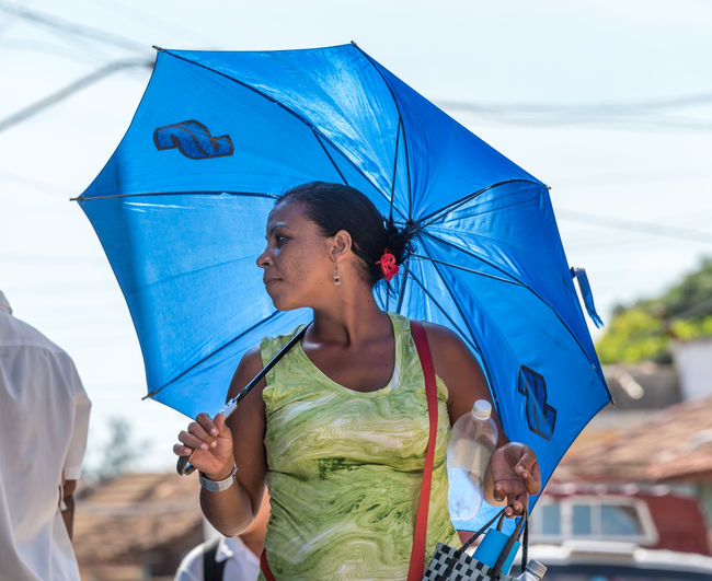 Cuban woman using an umbrella as protection against the afternoon sun Caribbean City Communism Cuba Cuban Every Day Everyday Female Heat Images Lifestyle Matanzas Protection Revolution S Scenes Summer Sun Sun Protection Umbrella Way Of Life Woman