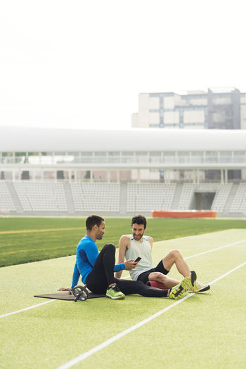 Male athletes sitting on grass against sky