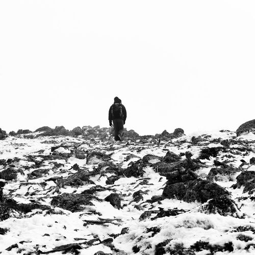 Rear view of man on snowcapped landscape against clear sky