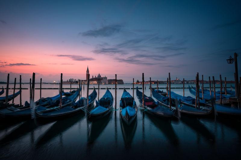 Gondolas in a row with chiesa di san giorgio maggiore in the background at sunrise in venice, italy