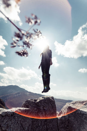 Low angle view of woman levitating on rock against sky