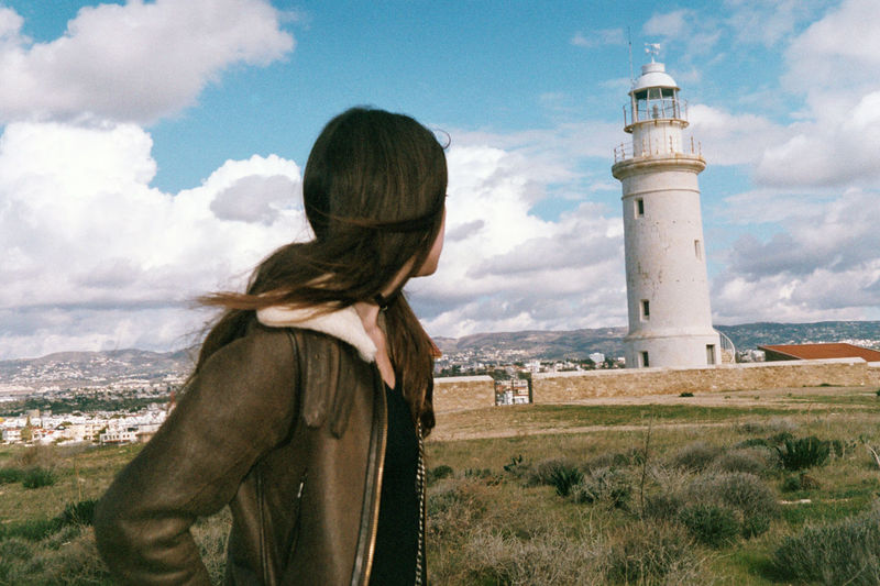 View of woman standing by lighthouse against sky