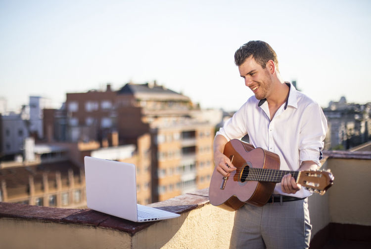 Young man playing guitar against sky in city