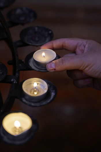 Cropped hand holding lit tea light candle in church