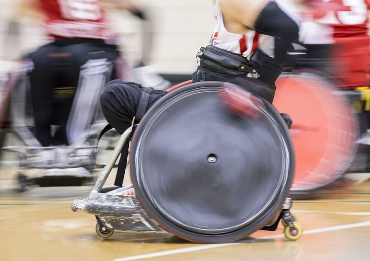 Blurred Motion Of Male Athletes Playing Wheelchair Basketball On Court
