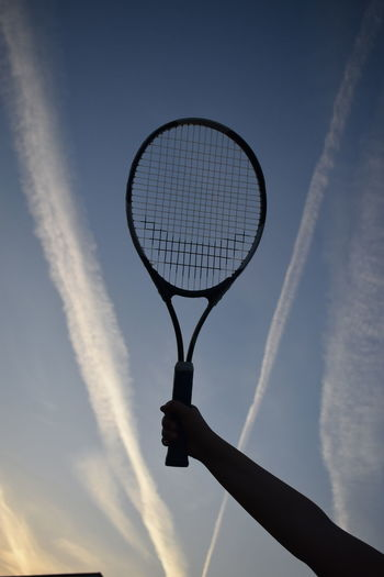 Low angle view of cropped hand holding tennis racket against sky