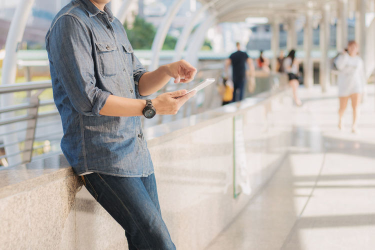Midsection Of Man Using Mobile Phone At Railroad Station