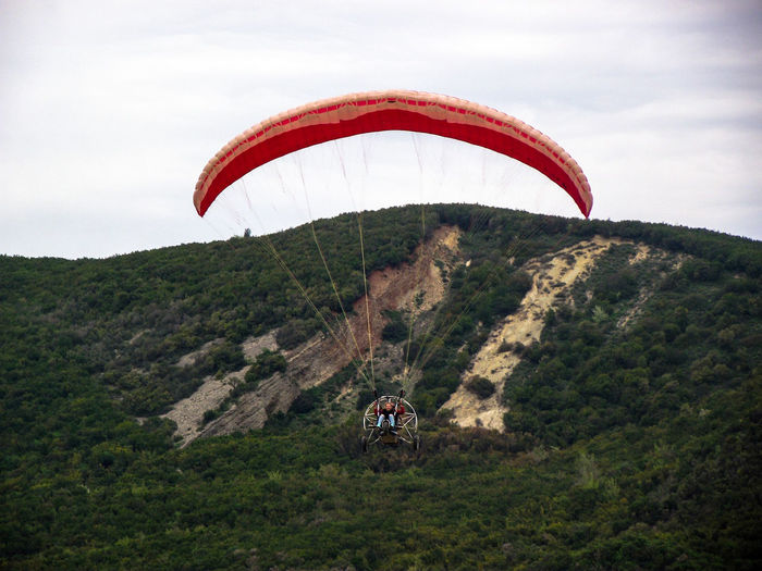 Woman parachuting over mountain against sky