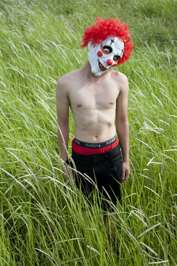 Young man wear the mask of clown on the grass. ASIA Asian  Fear Inward Masks Weird Young Asia People Clown Field Grass Green Color Internal Mask Mystery Nakedmen One Person Outdoors Psychology Real People Scary Scary Face Shirtless Wear Young Adult