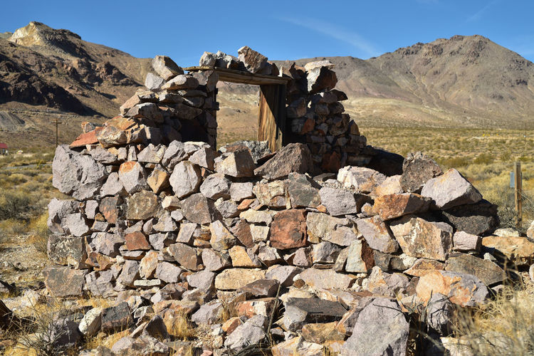 Stone wall on mountain against sky