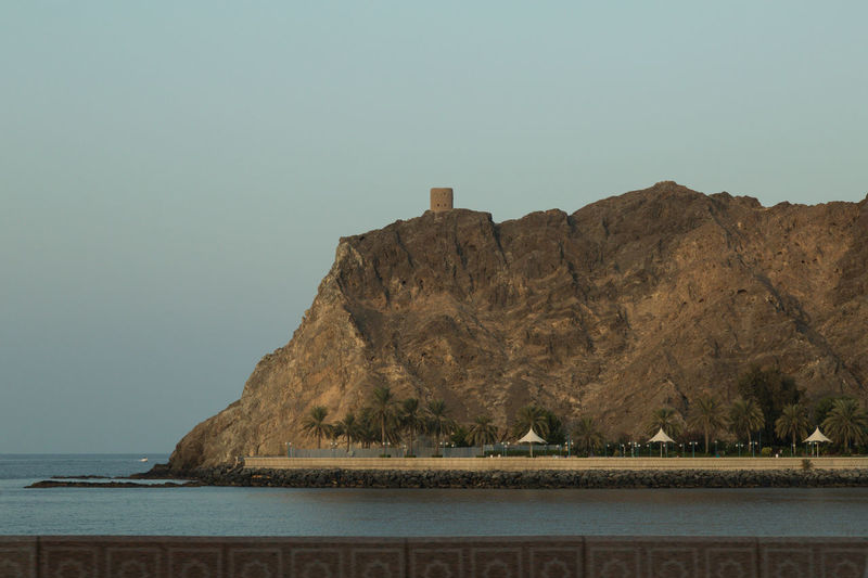 tower on an outcropping of rock in Muscat, Oman overlooking the Arabian Sea Arabian Sea Beach Beauty In Nature Blue Sky Day Landscape Landscapes Muscat , Oman Nature No People Outdoors Rock Formation Scenics Sea Sky Sultanate Of Oman Tower Water
