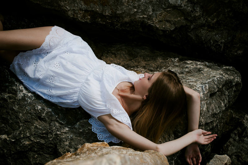 Young woman resting on rocks