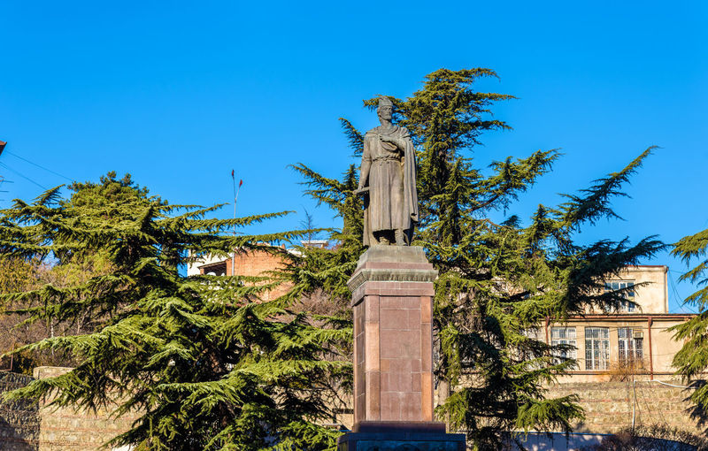 Low angle view of statue by building against blue sky