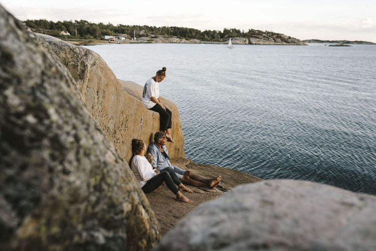 People sitting on rock by sea