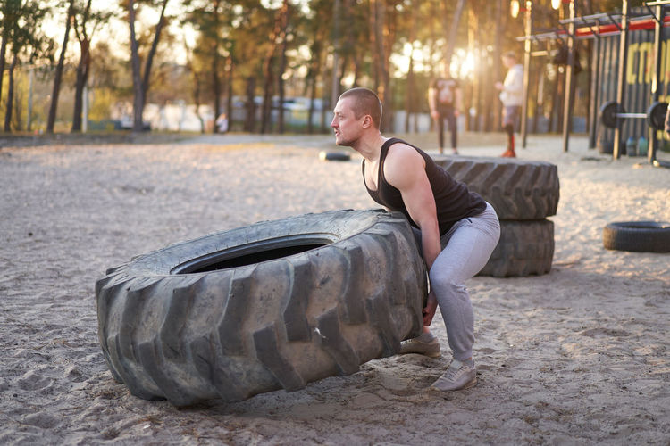 Full length of man exercising with tire on sand