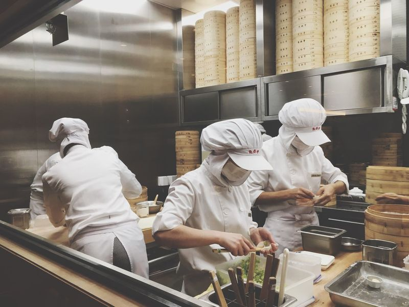Real People Commercial Kitchen Indoors  Occupation Working Men Preparation  Food And Drink Establishment Food And Drink Industry Uniform Food And Drink Factory Food Teamwork Women Skill  Standing Chef Chef's Hat Bakery