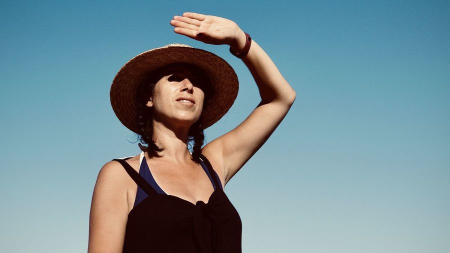 Low angle portrait of woman standing against clear blue sky