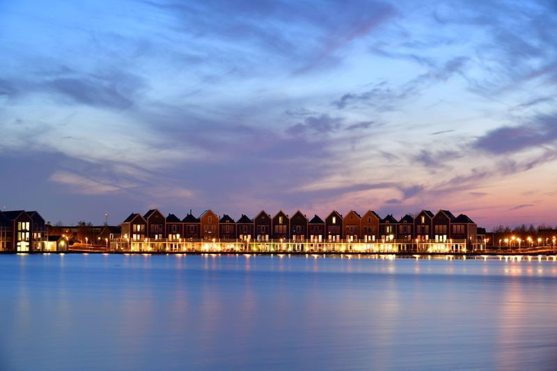 Illuminated buildings by lake against sky during sunset