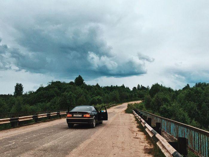 Car on road against cloudy sky