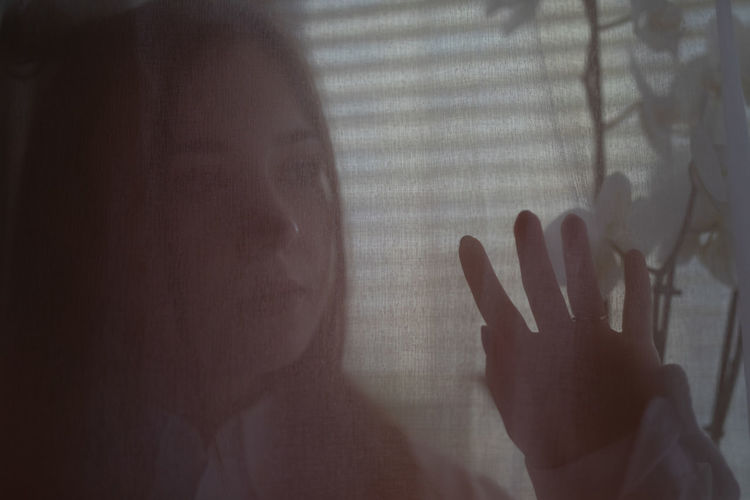 Close-up of hand touching glass window