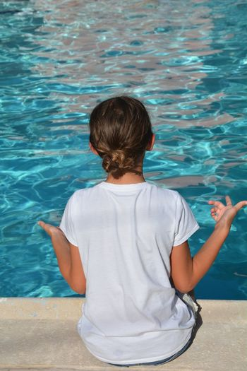 Rear View Of Girl Sitting Against Swimming Pool