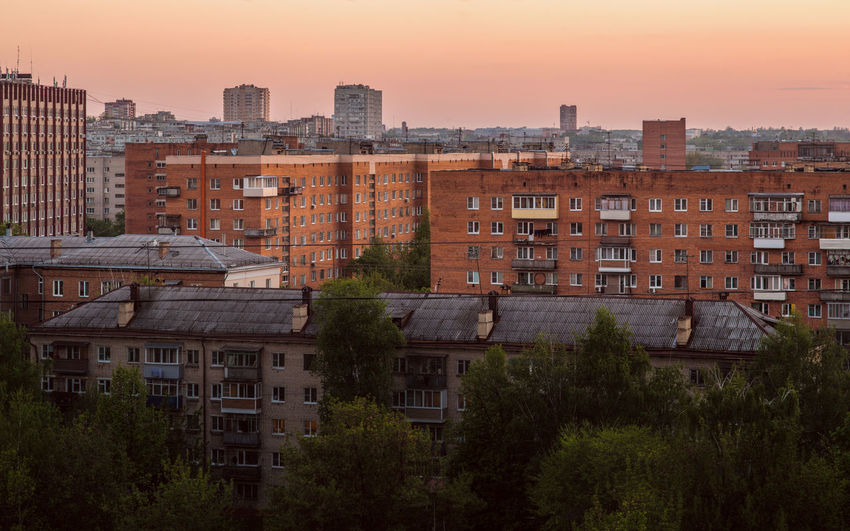 Residential buildings against sky at sunset