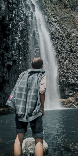 Rear view of man standing at waterfall in forest