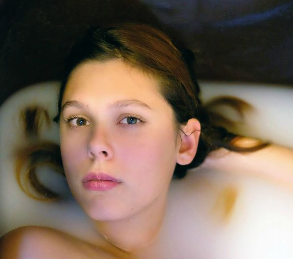 Close-up portrait of young woman in bathtub