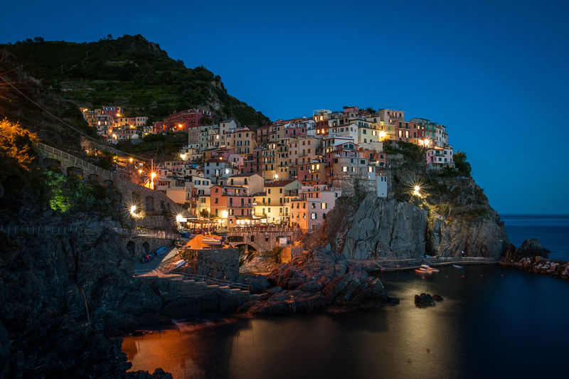 Illuminated town by sea against sky at night